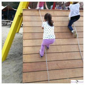 kind trekt zich omhoog door zich aan de ketting vast te houden