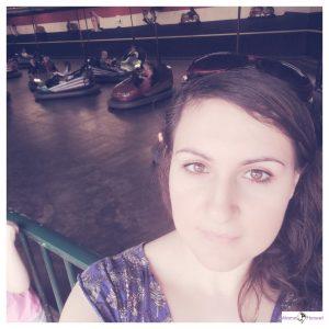 vrouw met zonnebril op staat voor de botsauto's