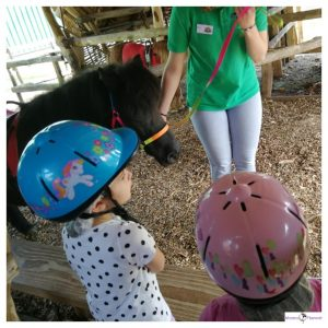 2 kinderen met helmen om krijgen instructie van de dame met een pony aan de hand
