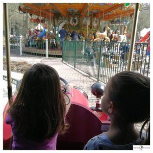 Kinderen kijken vanuit een oldtimer naar een draaimolen